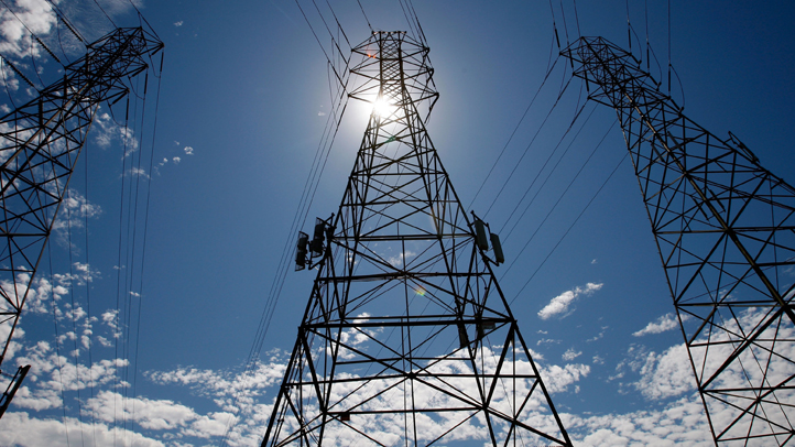 The sun shines over towers carrying electical lines.