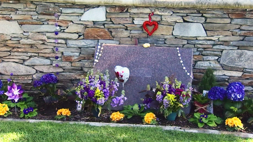 A grave with purple and gold flowers
