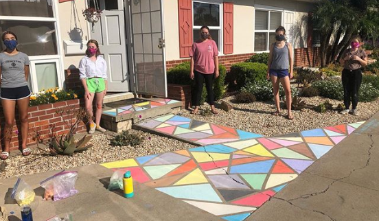 Members of the Rolando Chalk Project stand next to one of their artistic pieces.