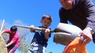 Boy scoops sand into sandbags