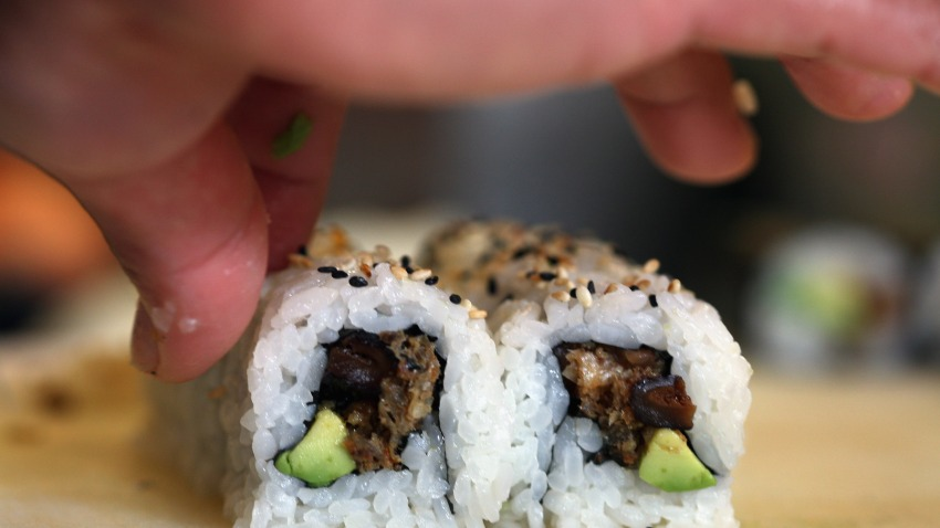 Sushi Rolls Fixed by a Hand