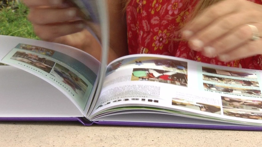 A Creative Performing and Media Arts Middle School student flipping through the yearbook.