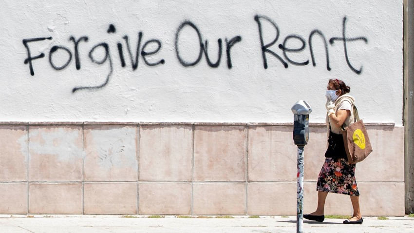 A woman wearing a mask walks past a wall bearing a graffiti asking for rent forgiveness on La Brea Ave on National May Day amid the Covid-19 pandemic, May 1, 2020, in Los Angeles, California.
