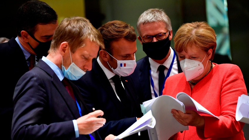 German Chancellor Angela Merkel, right, speaks with French President Emmanuel Macron, center, during a round table meeting at an EU summit in Brussels, Monday, July 20, 2020.