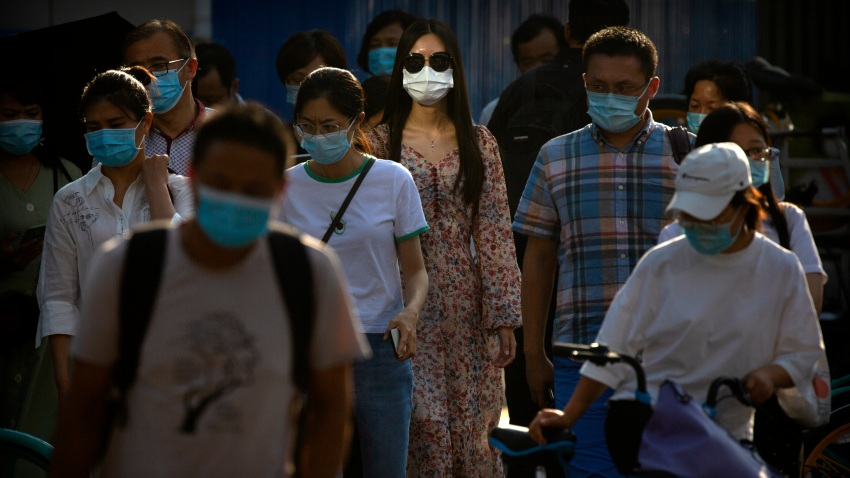 People wearing face masks to protect against the coronavirus wait to cross an intersection in the central business district in Beijing