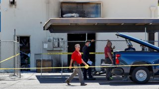 Fire investigators stand outside the Arizona Democratic Party headquarters Friday, July 24, 2020, in Phoenix. Fire investigators are looking into the cause of an early morning blaze that destroyed part of the Arizona and Maricopa County Democratic Party headquarters Friday.