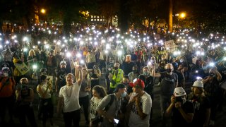Demonstrators raise their cell phone lights as they chant slogans during a Black Lives Matter protest at the Mark O. Hatfield United States Courthouse Wednesday, July 29, 2020, in Portland, Ore.