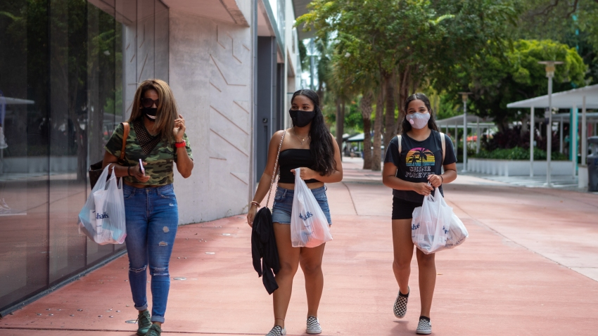 Shoppers carrying bags wear protective masks in Miami Beach, Florida, U.S., on Friday, July 17, 2020.