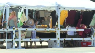 Merchants at a booth sell their items at Barrio Logan's Walk the Block initiative on Saturday, Aug. 9, 2020.