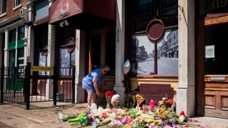 A woman lays flowers outside Ned Peppers bar in Dayton, Ohio