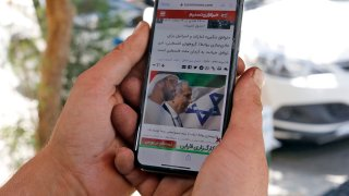 A man holds a phone while reading a story published on Tasnim News Agency's website about the recent news of a US-brokered deal between Israel and the UAE to normalise relations, in Iran's capital Tehran on August 14, 2020.