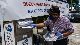 In this Aug. 18, 2020, file photo, poll workers help a voter put their mail-in ballot in an official Miami-Dade County drive- thru ballot drop box during Florida Primary Election amid the coronavirus pandemic, in Miami, Florida.