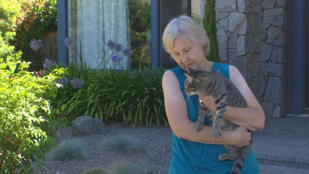 A woman holds a grey cat in her arms while standing in front of her home.