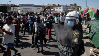 Migrants take part in a rally as riot police block the road near Mytilene town