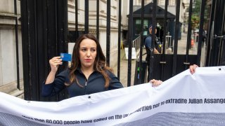 Partner of Wikileaks founder Julian Assange, Stella Moris, holds up a Julian Assange press card outside the gates of Downing Street, in Westminster, London, after attempting to deliver a Reporters Without Borders petition against the extradition of her partner to the US. Lawyers for Assange and the U.S. government will face off in London on Monday at an extradition hearing that was delayed by the coronavirus pandemic.
