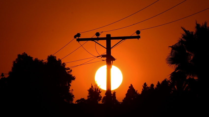 The sun sets behind power lines.