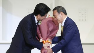 to outgoing Prime Minister Shinzo Abe (L) after the ruling LDP party's leadership election in Tokyo on September 14, 2020. - Japan's ruling party on September 14 elected chief cabinet secretary Yoshihide Suga as its new leader, making him all but certain to replace Shinzo Abe as the country's next prime minister.