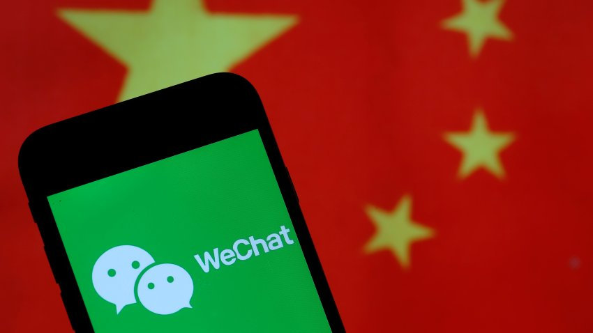 The WeChat logo is displayed on the screen of a smartphone in front of a Chinese flag