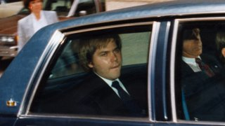 John Hinckley, Jr., accused assassinate of President Reagan, sits in the back of this motioned vehicle outside the federal court in DC shortly after asking for permission to visit his family for Easter without supervision, Jan. 1, 1990.