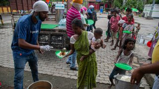 Indian homeless people stand in queue to receive free food distributed by the Sikh community near a railway station in Gauhati, India, Sunday, Sept. 6, 2020. India's coronavirus cases have crossed 4 million, leading the world in new infections and deepening misery in the country's vast hinterlands where surges have crippled the underfunded health care system.
