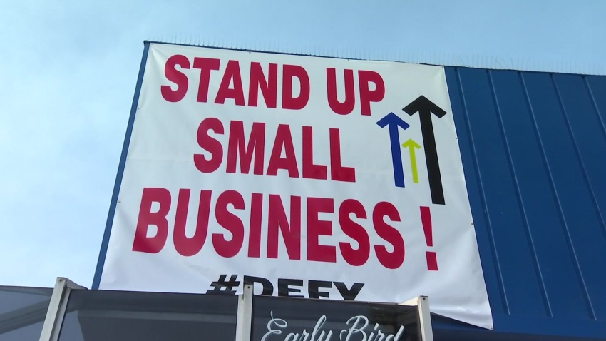 """A sign that reads, """"Stand Up Small Business #Defy"""" rests above Rudford's Restaurant."""