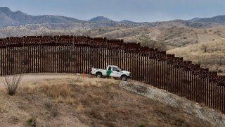 In this Feb. 9, 2019, file photo, a Border Patrol officer sits inside his car as he guards the US/Mexico border fence, in Nogales, Arizona.