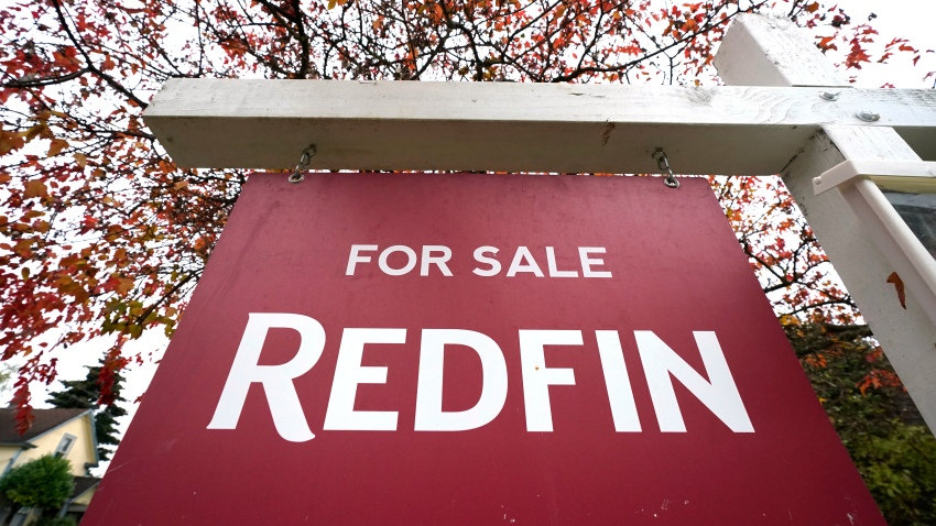 "A Redfin ""for sale"" sign stands in front of a house"