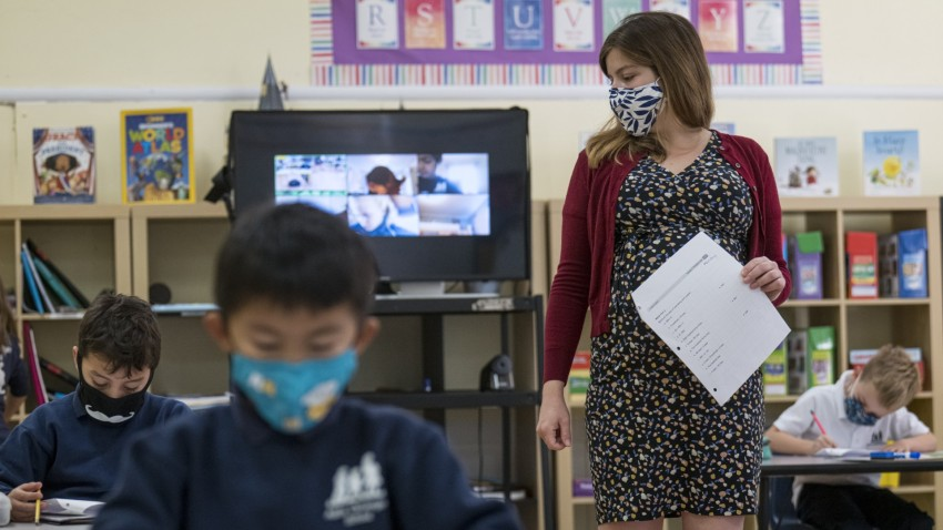A teacher wearing a protective mask walks around the classroom during a lesson at an elementary school in San Francisco.