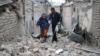 A man helps a woman get over the rubble left by shellfire