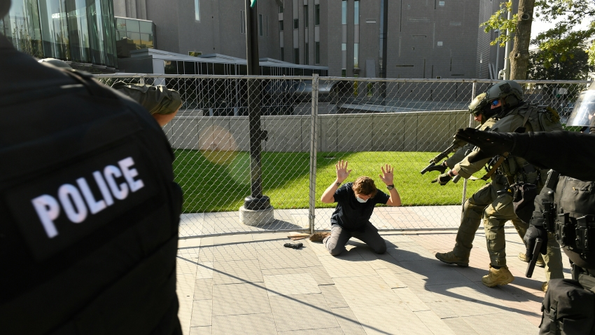 A man holds up his hands as he is taken into custody after fatally shooting another man in Denver, Colorado, on October 10, 2020. At the time two rallies, one right-wing and one left-wing, were taking place near one another. The man who died was participating in the right-wing rally. Denver Channel 9News has confirmed that the man who did the shooting was a private security guard contracted by them and is in custody after the shooting. It has been confirmed the guard was contracted through Pinkerton for the station.