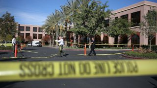 Officers put up police tape in front of the building at the Inland Regional Center where 14 people were killed on Dec. 7, 2015 in San Bernardino.