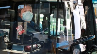 A San Diego MTS bus driver wears a mask behind a barrier from her seat.