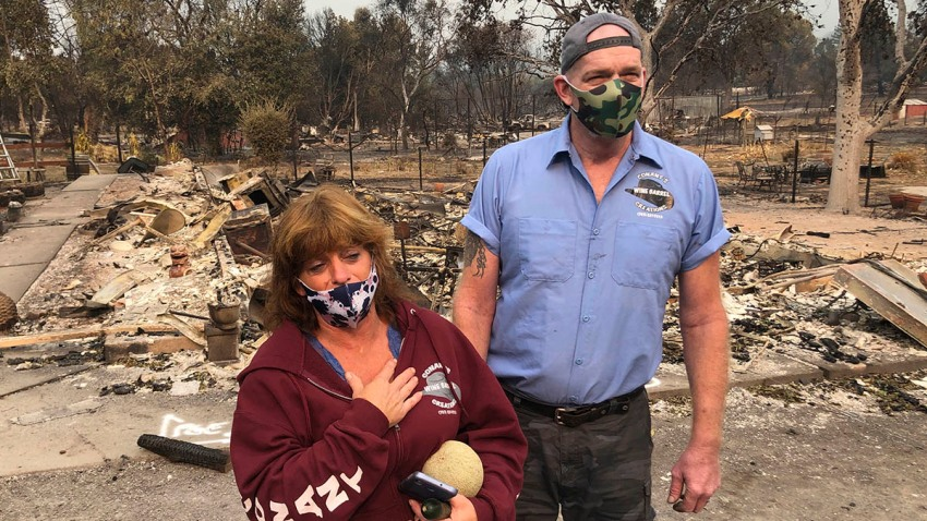 """Kevin Conant and his wife, Nikki, look at the debris of their home and business, """"Conants Wine Barrel Creations,"""" after the Glass/Shady Fire completely engulfed it, Sept. 30, 2020, in Santa Rosa, Calif."""