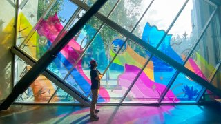 """Artist Regan Russell stands before his new mural """"Energized"""" at the New Children's Museum in Downtown San Diego."""