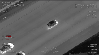 A still image taken from SDPD helicopter footage showing the suspect's car stopped on the freeway with officer vehicles close behind.