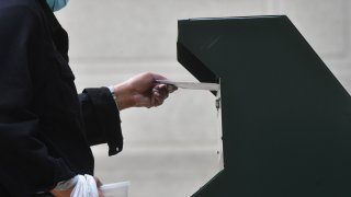 A woman deposits her ballot in an official ballot drop box at the satellite polling station outside Philadelphia City Hall on October 27, 2020 in Philadelphia, Pennsylvania.