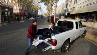 Ryan Breakfield and his girlfriend Erica Everett have lunch in the bed of a pickup after they were unable to eat inside a restaurant in Lodi, California, Dec. 9, 2020. California's San Joaquin Valley has the fewest available intensive care unit beds of any region in California, a frightening reality that health officials hope will convince more people to wear masks and socially distance.