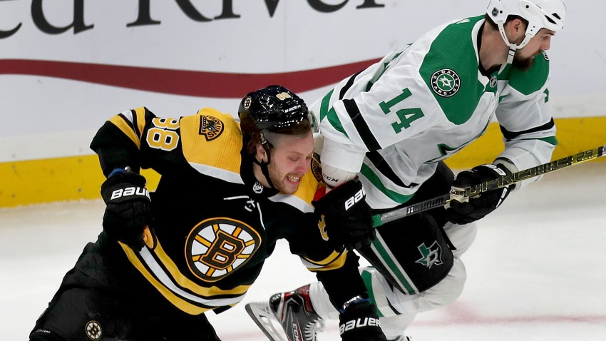 BOSTON - FEBRUARY 27: Boston Bruins right winger David Pastrnak and Dallas Stars left winger Jamie Benn fight for a loose puck in the first period. The Boston Bruins host the Dallas Stars during a regular season NFL hockey game at TD Garden in Boston on Feb. 27, 2020.