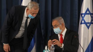 """Israeli Prime Minister Benjamin Netanyahu (R) speaks with Alternate PM and Defence Minister Benny Gantz, both wearing protective mask due to the ongoing COVID-19 pandemic, during the weekly cabinet meeting in Jerusalem on June 7, 2020. - Netanyahu urged world powers to reimpose tough sanctions against Iran, vowing to curb Tehran's regional """"aggression"""" hours after another deadly strike on pro-Iranian fighters in Syria. (Photo by Menahem KAHANA / AFP)"""