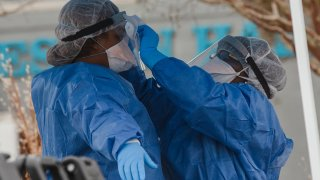 Healthcare workers from the Medical University of South Carolina clean each other's gear at a COVID-19 testing site in a parking lot