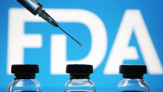 Vials and a medical syringe seen displayed in front of the Food and Drug Administration (FDA) of the United States logo.