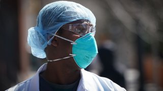 A healthcare worker wears a N95 respirator with two straps that fit around the head.