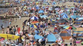 People gather on the beach during hot weather in Bournemouth, southern England, Sunday Aug. 9, 2020. Many Britons are set to bask in another hot day, with clear skies and hot temperatures predicted to continue.