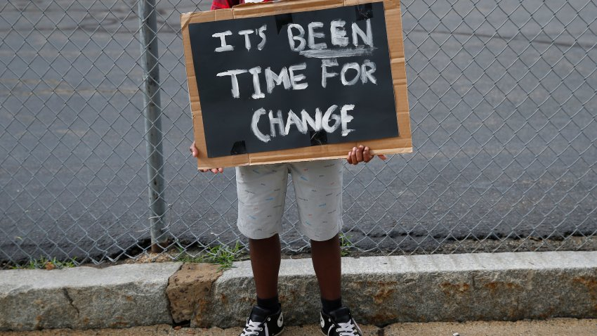 Dewayne Henry, 14, holds a sign as he protests outside of Mystic Valley Regional Charter School in Malden, MA