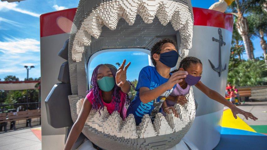Children wearing face masks play at Legoland California Resort.