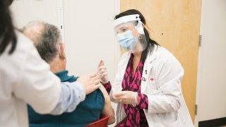 famrmacéutica administrando la vacuna contra el covid-19 a un paciente.