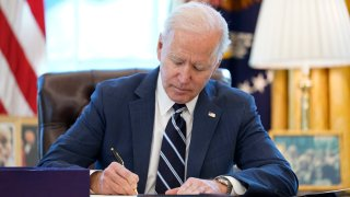 In this March 11, 2021, file photo, President Joe Biden signs the American Rescue Plan, a coronavirus relief package, in the Oval Office of the White House in Washington, D.C.