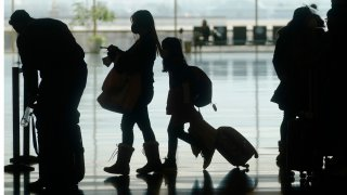 Travelers walk through the Salt Lake City International Airport Wednesday, March 17, 2021, in Salt Lake City. Airlines and others in the travel industry are throwing their support behind vaccine passports to boost pandemic-depressed travel, and authorities in Europe could embrace the idea quickly enough for the peak summer vacation season.