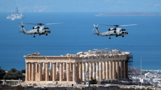 Military helicopters fly over Acropolis Hill during a military parade in Athens