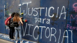 """Young women place flowers on the perimeter wall of the Quintana Roo state offices sprayed with graffiti that reads in Spanish """"Justice for Victoria,"""" during a protest in Mexico City, Monday, March. 29, 2021. The demonstrators were protesting the police killing in Tulum, Quintana Roo state, of Salvadoran national Victoria Esperanza Salazar when a female police officer knelt on her back to cuff her. Mexican authorities say an autopsy confirmed that police broke her neck."""